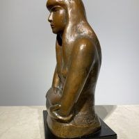 Bronze sculpture of a girl with crossed arms, side view