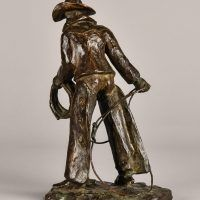 Bronze sculpture of a standing cowboy with lasso, angled view
