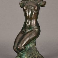 Bronze sculpture of a headless and armless seated female nude