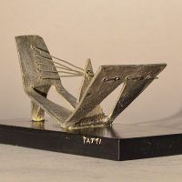 Abstract soldered lead sculpture atop a wooden base resembling a drawbridge, angled view
