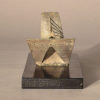 Abstract soldered lead sculpture atop a wooden base resembling a drawbridge, frontal view