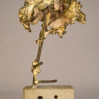 Welded bronze sculpture shaped like a tree mounted on a slag block, side view