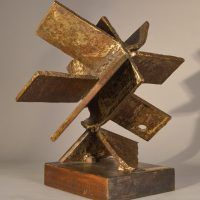 Welded steel sculpture with many panels or blades, resembling a fan, angled view