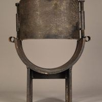 Steel sculpture in the shape of a small chair with rounded seat, rear view