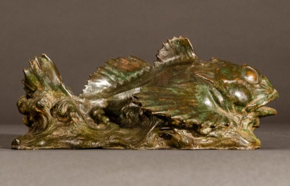 Bronze sculpture of a sculpin fish atop the water, side view