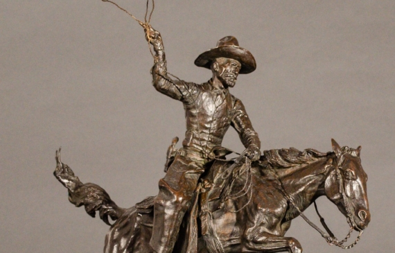 Bronze sculpture of a cowboy with a lasso riding a horse jumping over a cactus