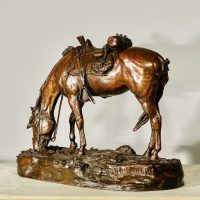 Bronze sculpture of a saddled horse bending down to graze, angled view