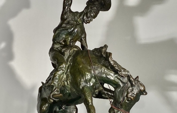 Bronze sculpture of a cowboy riding on a bucking bronco, side view