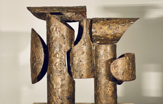 Abstract bronze and steel assemblage mounted on a stone block, rear view