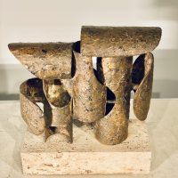 Abstract bronze and steel assemblage mounted on a stone block, downward view