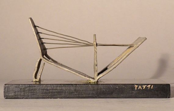 Abstract soldered lead sculpture atop a wooden base resembling a drawbridge, side view