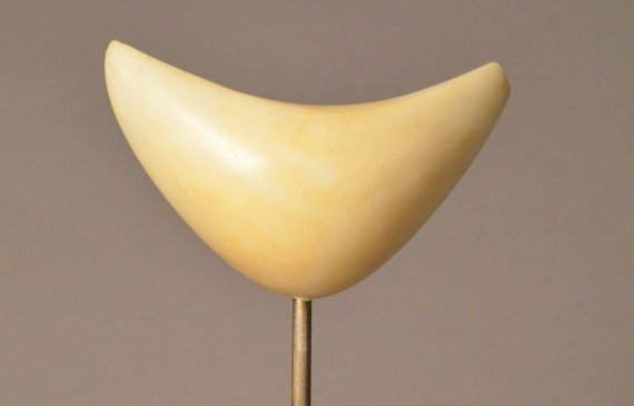 Boomerang-shaped marble sculpture mounted on marble, attached by a short metal poll