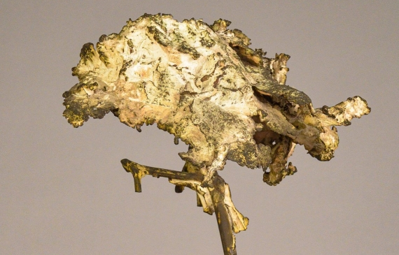 Welded bronze sculpture shaped like a tree mounted on a slag block, angled view
